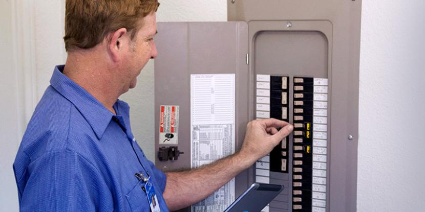 A technician in a blue shirt flipping a switch on a breaker box.