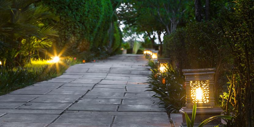 A picture of path lights on each side of a walkway surrounded by landscape