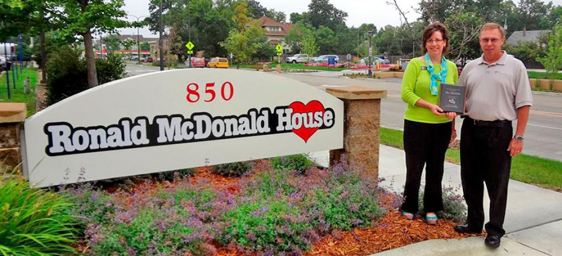 Image of couple holding award in front of Ronald McDonald House sign